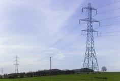 Grands pylônes et câbles portant l'électricité produite à la puissance Stationy de Ballylumford dans la grille Images libres de droits