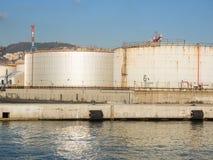 Grands réservoirs de stockage de pétrole dans le port pétrochimique, se reflétant dans l'eau Image libre de droits