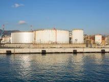 Grands réservoirs de stockage de pétrole dans le port pétrochimique, se reflétant dans l'eau Images stock
