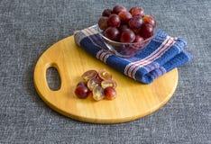 Grands raisins dans un bol en verre, raisins coupés photos stock