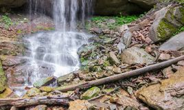 Grands rochers et rondins au pied de la cascade Photos stock