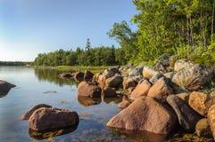 Grands rochers sur le bord de mer au coucher du soleil Images stock