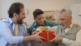 Grandson closing grandpa eyes, father giving gift box, birthday surprise, family