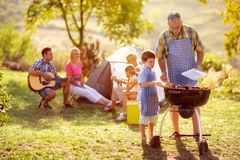 Grandson cooking on campfire with grandfather stock photography