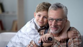 Grandson cuddling grandfather with love, precious family minutes, elderly care. Stock photo royalty free stock photos