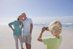 Grandson with digital camera photographing grandparents on sunny beach royalty free stock images