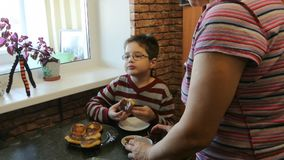 Grandson eats at grandma`s cottage cheese pancakes with honey. stock footage