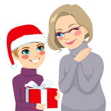 Grandson Giving Present To Grandmother. Happy grandson in Christmas day giving present to lovely grandmother Royalty Free Stock Photo