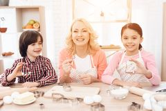 Grandson and granddaughter together with happy grandmother are engaged in cooking in kitchen. Beautiful young granny is sitting in kitchen with her little Stock Photos