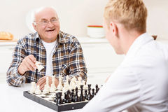 Grandson and grandfather playing chess in kitchen Stock Photo