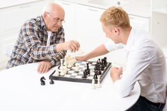 Grandson and grandfather playing chess in kitchen Royalty Free Stock Photo