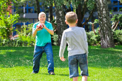 Grandson And Grandfather Playing Rugby Stock Photos