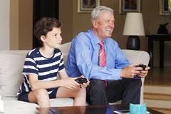 Grandson and grandfather playing together Stock Image