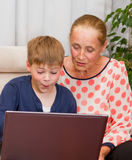 Grandson and grandmother loking at laptop Stock Images