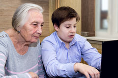 Grandson grandmother teaches computer literacy Royalty Free Stock Photos