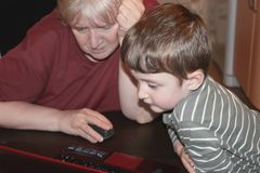 Grandson and grandmother using a computer at home royalty free stock photos