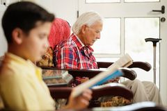 Grandson And Grandpa Reading Book And Relaxing At Home. Family relationship between grandfather and grandson. Grandpa and male grandchild reading book at home Stock Photos
