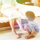 Grandson helping grandmother at home in bedroom Stock Images