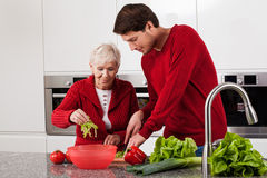 Grandson helping in kitchen. Adult grandson helping his grandma in kitchen stock photography
