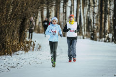 Grandson and his grandmother running through winter woods together Stock Photography