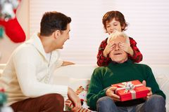 Grandson holding eyes of grandfather closed. Grandson holding the eyes of his grandfather at christmas closed Stock Image