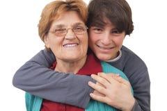Grandson hugging grandmother Stock Images