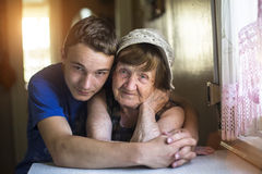 Grandson hugging her grandmother in their home. Stock Images