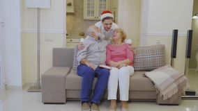 Grandson hugs grandparents. Elderly people hugs and sits on couch in living room at home. Senior man talks with his wife. Young grandson in Santa`s hat comes to stock footage