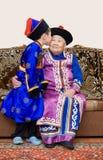Grandson kisses his great grandmother. Buryat (mongolian) great grandmother and her grandson, in national costumes Stock Photography