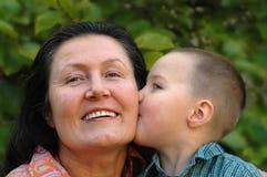Grandson kissing his granny. Young grandson giving his grandma a big smooch on the cheek Stock Image
