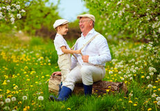 Grandson playing with grandpa, pulling the braces, spring garden Stock Image