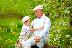 Grandson playing with grandpa in spring garden Stock Photo