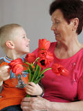 Grandson present flowers to grandmother Stock Images