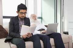 Grandson reading book while grandfather using laptop on sofa at home Royalty Free Stock Photos