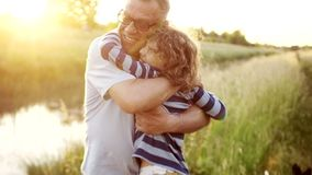 The grandson resorts to his grandfather. Joyful meeting on the river bank. Family weekend. Colorful sunset.  stock footage