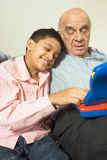 Grandson resting head on grandfather - Vertical Stock Image