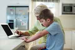Grandson using laptop with grandmother Royalty Free Stock Images