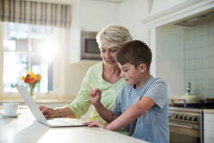 Grandson using laptop with grandmother Stock Photography