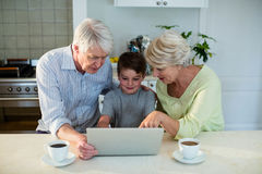 Grandson using laptop with grandparents Stock Photography