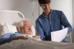 Grandson visiting grandpa in hospice. Photo of grandson visiting grandpa in hospice royalty free stock image