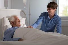 Grandson visiting grandpa in hospital. Picture of grandson visiting grandpa in hospital stock images