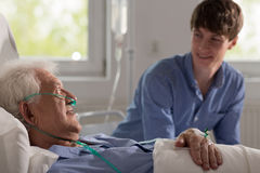 Grandson visiting ill grandfather Stock Photos