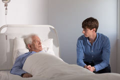 Grandson visiting ill grandpa. Staying in hospital royalty free stock photos