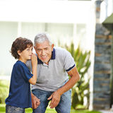 Grandson whispering secret in ear Royalty Free Stock Photography