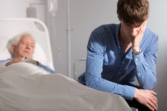Grandson worried about ill grandfather. Grandson worried about his ill grandfather in hospital Royalty Free Stock Photography