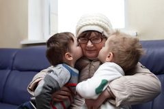 Grandsons kissing their grandmother Royalty Free Stock Image