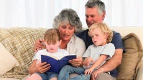 Grandsparents lisant un livre à leurs petits-enfants banque de vidéos