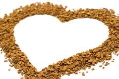 Granelli asciutti del caffè istantaneo sotto forma di un cuore - struttura marrone fotografia stock