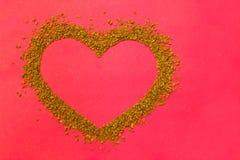 Granelli asciutti del caffè istantaneo sotto forma di un cuore - struttura marrone fotografie stock