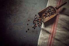 Granelli di pepe assortiti secchi in un mestolo di legno Fotografia Stock